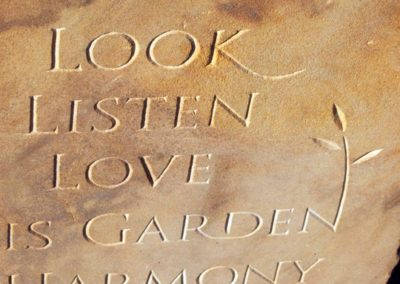 Hand-carved lettering on sandstone garden sculpture