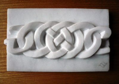 Celtic love knot with initials carved in marble