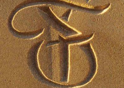 Hand-carved initials on sandstone garden sculpture